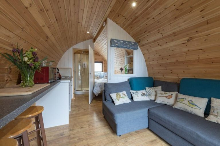 Glamping Pod with a light wood ceiling, a blue sofa, dining table and with a bed and bathroom at the back