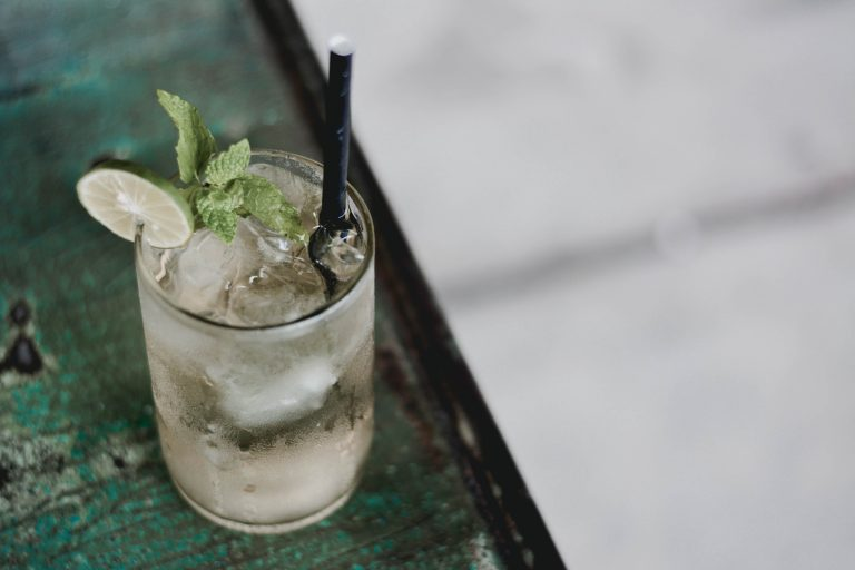 Mojito drink with a black straw and mint garnish