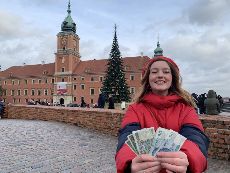 Woman holding Polish money out in front of her whilst standing in front of a grand building in a square in Warsaw