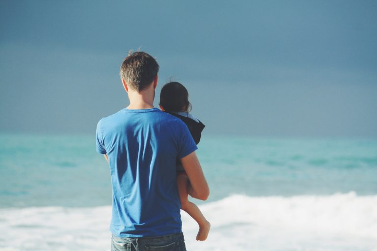 Father holding child at the beach